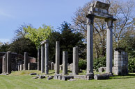Photograph of the ruins brought from the Roman city of Leptis Magna in the Libyan desert to be reconstructed in the early 19th century at Virginia Water under the directorship of Wyatville. Corinthian columns support pedestals of stone together with half broken columns both standing and lying on the ground.